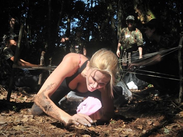 Mulher se arrastando na lama em curso de sobrevivencialismo